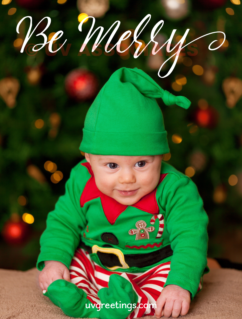 Baby wearing a green elf dress to wish you to be merry